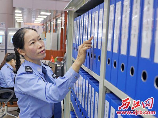 冯晓梅在业务窗口查看档案资料。 西江日报记者 吴威豪 摄