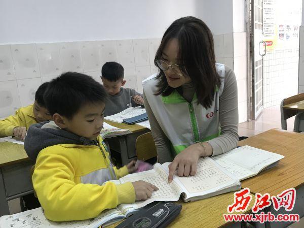 项目志愿者在辅导沙湖小学学生写作业。 西江日报记者 潘粤华 摄
