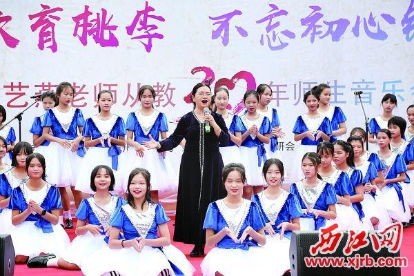 郭艺燕老师与学生们同台演唱。 西江日报记者 梁小明 摄