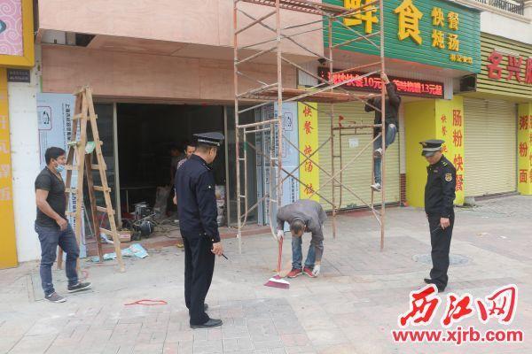 城管执法队员发现有商家未经批准占道施工,马上对其进行制止。 西江日报记者 严炯明 摄