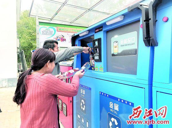 社播村村民將玻璃瓶子放進智能垃圾分類回收箱。 西江日報記者 潘粵華 攝
