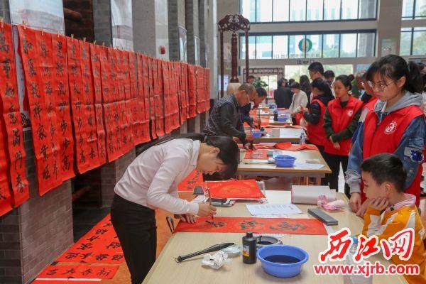 文化志愿者挥毫书写春联。 西江日报记者 曹笑 摄