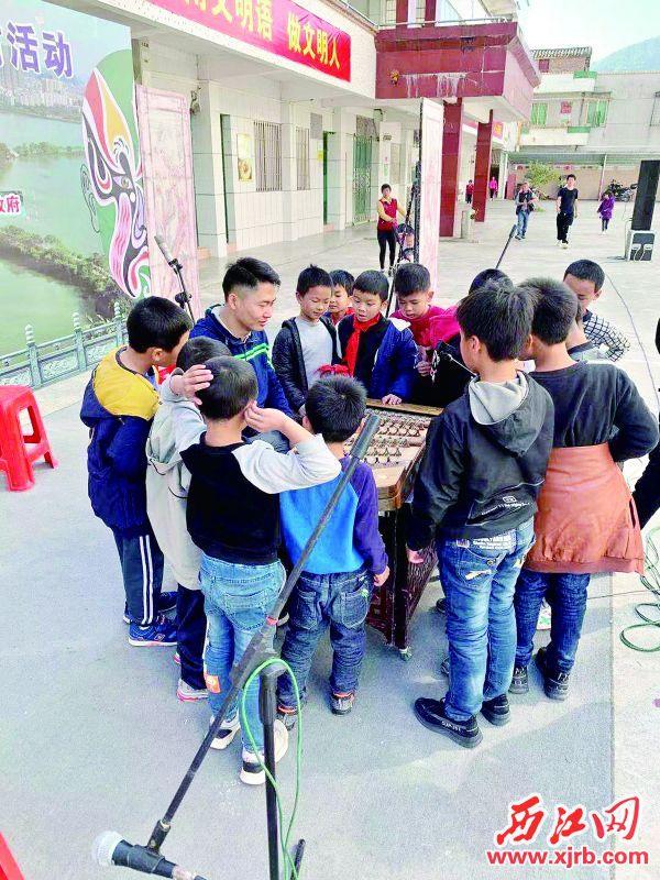 孩子们好奇地围住粤剧奏乐老师。