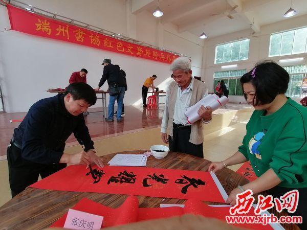 书法家为居民义写春联。 西江日报通讯员供图