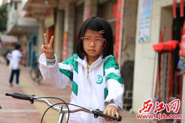 孤儿谢钰萍得到梦寐以求的自行车。 西江日报记者 杨丽娟 摄