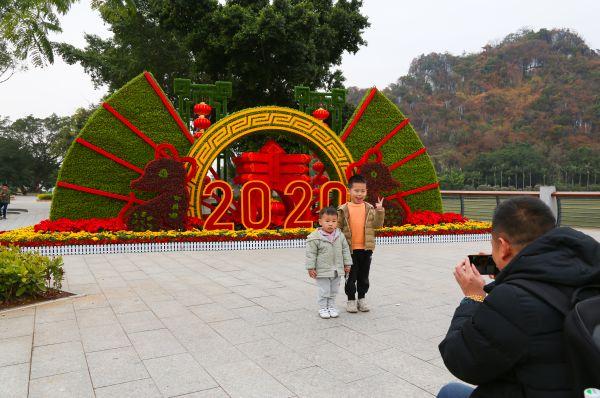 在倚岩公园市民游客在新布置的绿化景组前拍照留影。
