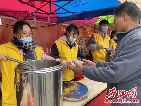 工会志愿者为返乡务工人员盛递热粥。 西江日报记者 刘浩辉 摄