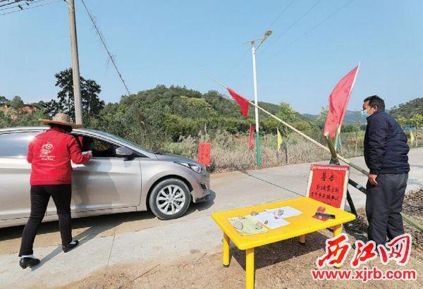 德慶縣永豐鎮斗村村的防控點,志愿者對出入的村 民進行登記。