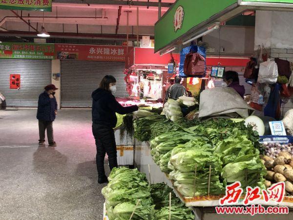 菜攤前,蔬菜按規定擺放整齊。商家和前來買菜的市民都有戴好口罩。楊樂祺攝