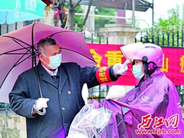 钟鉴强为居民检测体温。 靠谱的lol博彩app记者 吴威豪 摄