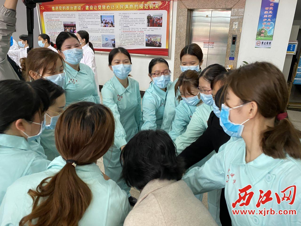 出发前,四会市中医院医疗队员相互打气。记者 周仪 摄