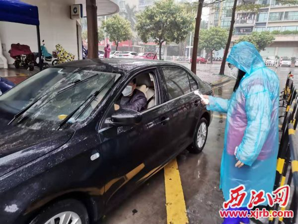 伍彩萍(右一)對進出社區的人員進行體溫檢測。 通訊員供圖