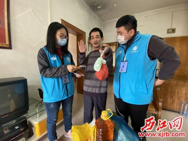 义工们帮忙买回生活物资,让陈健洪(中)很开心。 西江日报记者 赖小琴 摄