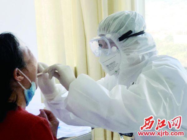 段红萍护士长为患者进行咽拭子检查。