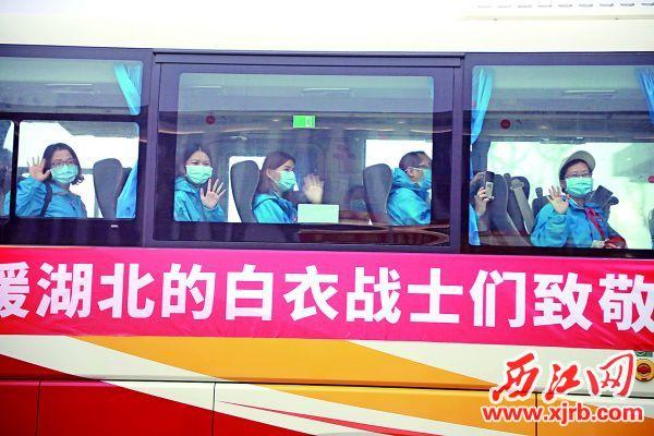 昨日,我市第一批返回的支援湖北医疗队队员向迎接人员挥手致意。 西江日报记者 刘春林 摄