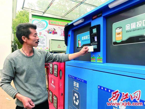 新塘村村民张学聪拿出专属的二维码 IC卡刷卡,以打开智能垃圾分类回收箱的 箱口投放玻璃瓶。  西江日报记者 潘粤华 摄