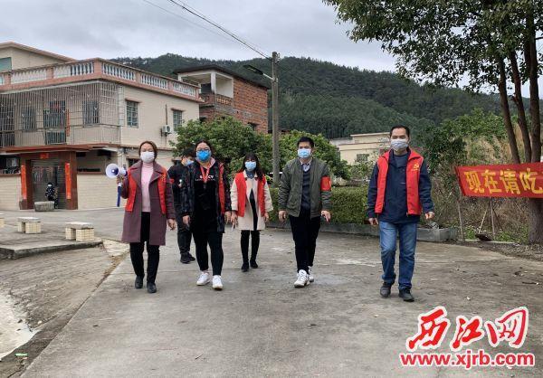 刘素华(左一)带领村委干部进行抗疫宣传。 通讯员 黄之栩 摄