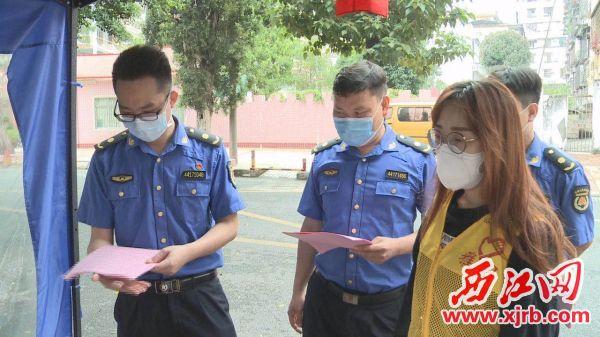 随车的城管队员向社区防疫点派发市疫情防控指挥部印发的《关于疫情期间暂停清明祭扫活动的通告》。通讯员供图