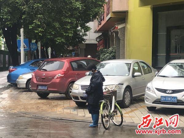 州区跃龙路口的一名骑车市民停下车,低头默哀。