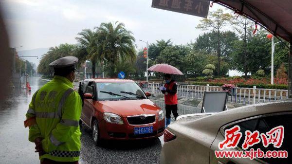 """2月15日,肇庆市""""西江党旗红""""党员突击队队员雨中坚持在防疫卡点执勤。"""