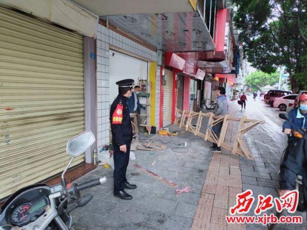 城管执法队员督促商铺负责人清理现场。通讯员供图