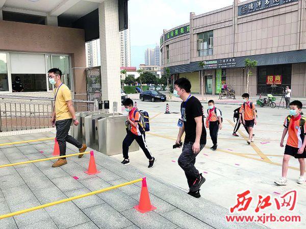 肇庆市奥威斯实验小学(新华校区)学生在教师带 领下进入学校。 西江日报记者 苏燕君 摄