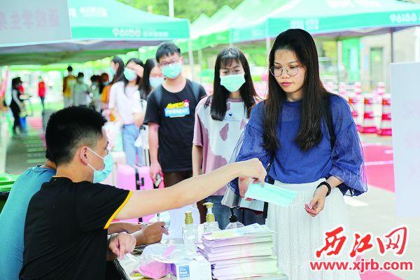 5月18日,肇庆学院首批学生返校,注册登记后老师给学生发放口罩。 西江日报记者 梁小明 摄