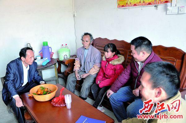 李德明(左)带队探访特困户。 西江日报通讯员供图