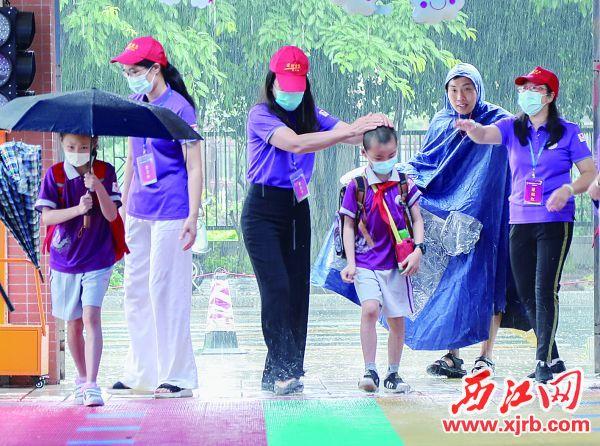 昨日上午,市第十六小学明月校区老师在校门口 迎接返校学生。 西江日报记者 梁小明 摄