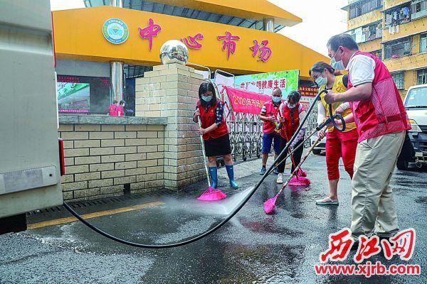 志愿者在清扫市场周边。 西江日报记者 曹笑 摄