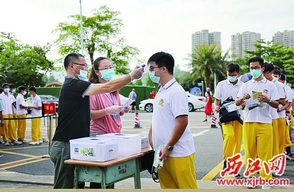 7月7日上午,工作人員在肇慶中學高中部考點門口為考生測量體溫。 西江日報記者 梁小明 攝