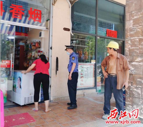 高要区城管执法队员劝导锦伦 街横街一商户纠正占道经营行为。  通讯员供图