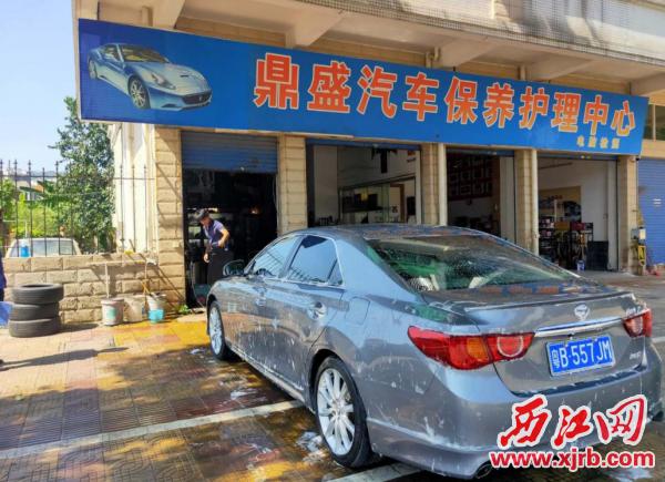 鼎湖区一汽车保养店占用人行 道洗车。 通讯员供图