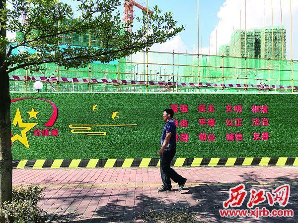 """南湖明珠花园的建筑工地围挡已换上公益广告""""新衣""""。 充值100送18记者 夏紫怡 摄"""