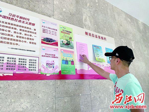 """端州区和平社区在小区楼道设置了便民信息栏,方便群众获取信息,减少 """"牛皮癣""""。 西江日报记者 潘粤华 摄"""