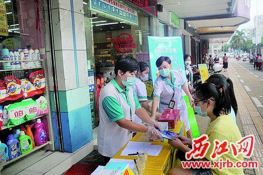 工作人员将礼品口罩交到市民手上。 西江日报记者 严炯明 摄