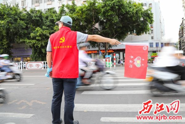 身穿红色马甲的志愿者,协助交警疏 导交通,引导市民文明出行。 西江日报记者 梁小明 摄