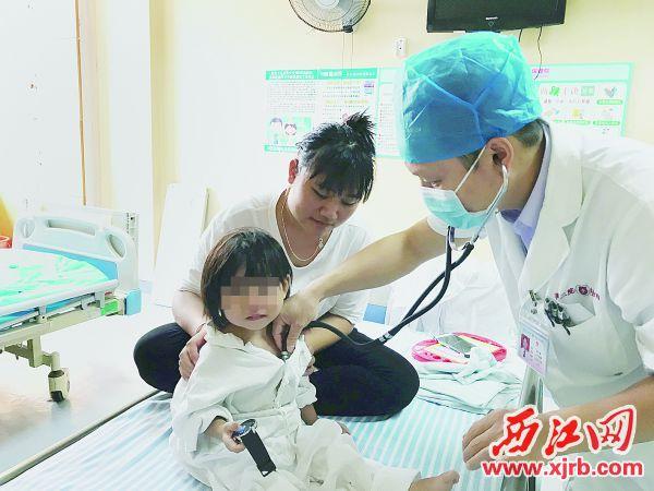 市二醫院心內科主任醫師翟永新為一名先天性心臟病患兒檢查。  西江日報記者 嚴炯明 攝