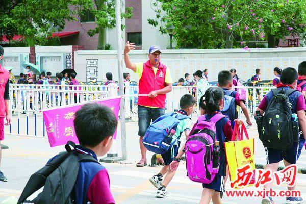 周水义风雨无阻在校门口守护孩子们的安全。 西江日报通讯员 孙姝 摄