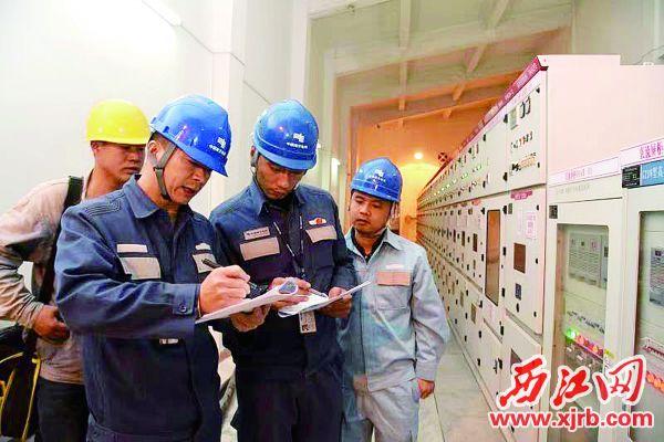 梁志刚(前左一)和同事在检查 肇庆市体育中心的电房设备。 受访者供图