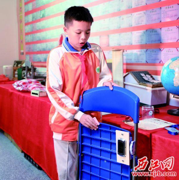 冼俊锦和他发明的防霸座座椅。  西江日报记者 杨丽娟 摄