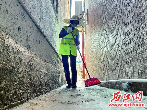 高要区南兴一路楼房间狭窄的通道里,保洁员陈玲在认真清扫。 西江日报记者 赖小琴 摄