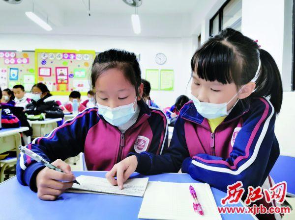 小先生(右)在教小徒弟。 西江日报记者 杨丽娟 摄