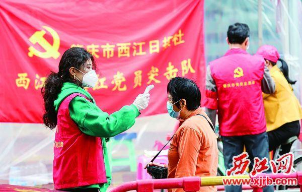 """""""西江党旗红党员突击队""""志愿者在端州城区疫情防控点检测群众体温。  西江日报记者 梁小明 摄"""