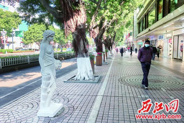 一名行经路人注视着一旁的雕像。 西江日报记者 严炯明 摄