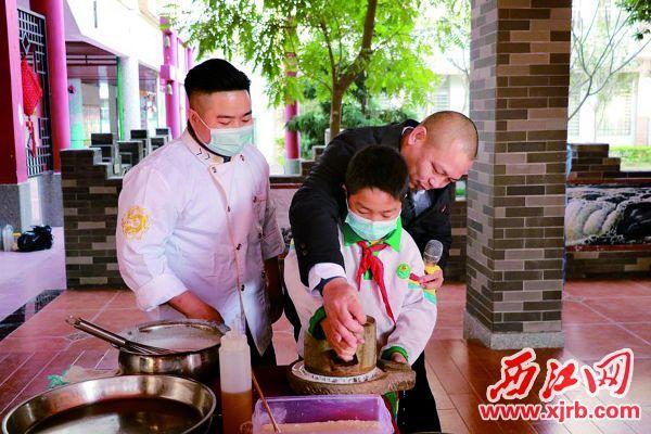 疍家糕制作技 艺代表传承人彭智 勇(右一)现场指导 同学磨浆。 西江日报通讯 员梁海燕 摄