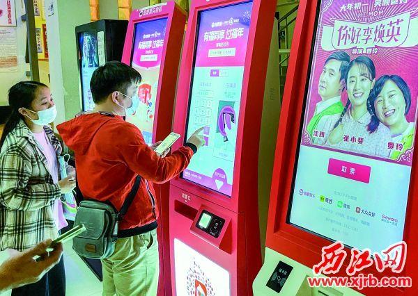 观影市民正在无接触购票。 西江日报记者 曹笑 摄