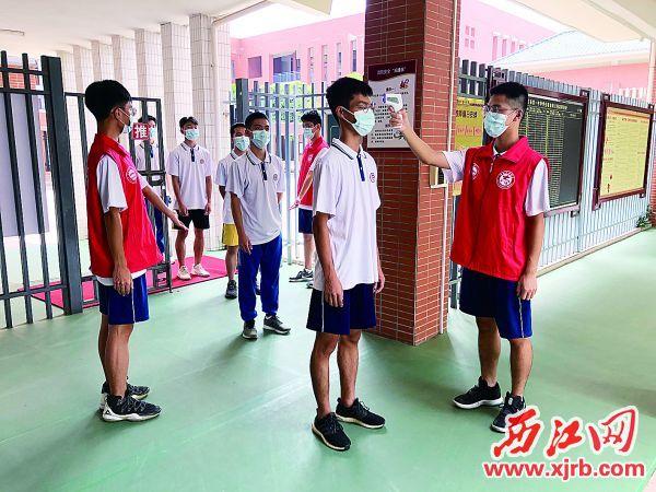 市一中的学生志愿者参加返校复学志愿服务,为进校学生测温。受访单位供图