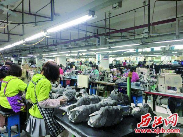 广宁县中保鞋业的工人们忙碌地工作。 西江日报通讯员 宁功 摄