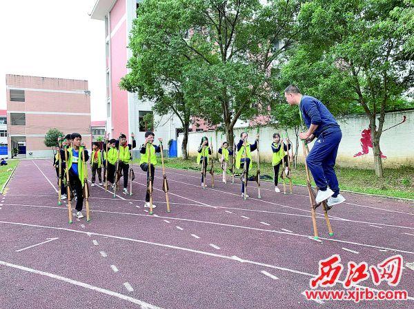 怀集县下帅乡民族学校副校长马倍修在教学生学习高脚竞速。 受访者供图